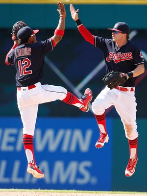 Cleveland Indians' Francisco Lindor (12) and Tyler Naquin celebrate a 8-0 win over the Oakland Athletics during in a baseball game Sunday, July 31, 2016, in Cleveland. (AP Photo/Ron Schwane)