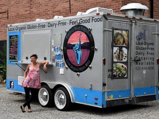 Katie DiLibero, co-owner of Cafe DeLuxe with her husband Rich Selden, strikes a pose alongside their Electric Blue Elephant vegan food truck. Some of the dishes from the truck they added to the Cafe DeLuxe menu when they bought the restaurant in late 2014.
