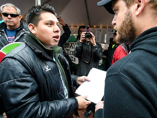 Enrique Balcazar, left, delivers a letter to Ben & Jerry's scoop shop manager Ryan Midden as members of Migrant Justice demonstrate during the ice cream company's Free Cone Day on Tuesday, April 4, 2017. The letter is intended for Ben & Jerry's CEO Jostein Solheim.