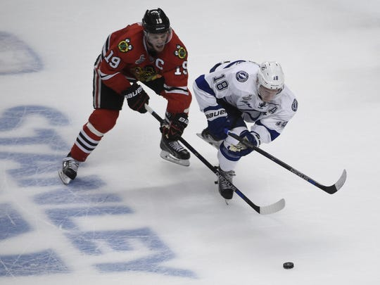 Blackhawks center Jonathan Toews (19) and Lightning left wing Ondrej Palat (18) chase after the puck during the third period of Game 4 of the Stanley Cup Final at United Center.