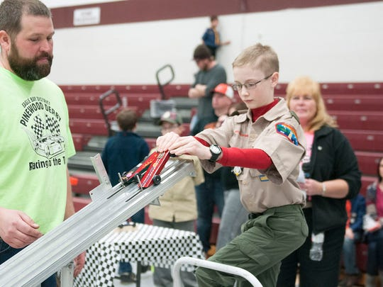 Collin Stull, 11, of Clyde, places his pinewood derby car on the track during Sunday's Eagle Bay District Pinewood Derby at Genoa Area High  School. Stull, a member of Pack #320, was the overall winner of the event.