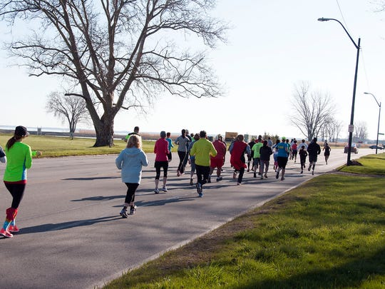 "Runners and walkers started off on East Perry Street near Adams Street Park during the ""Superhero 5K"" on Sunday morning."