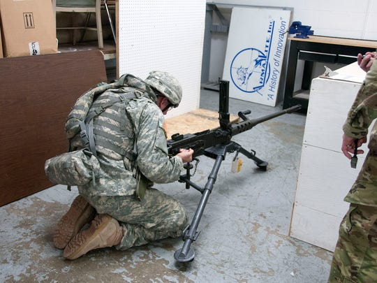 """Ohio Army National Guard Staff Sgt. Matthew Paul, 637th Chemical Company, Kettering, disassembles a M250 caliber firearm as part of the """"Best Warrior Competition"""" at Camp Perry on Tuesday. Fourteen soldiers from across seven states participated in the 15th annual event."""