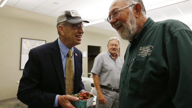 Sen. Chuck Grassley, left, shares a laugh with Bob Swindell on Friday, May 29, 2015, after Swindell presented Grassley with fresh strawberries after a town hall meeting in Mount Pleasant, Iowa. ** Corrected from previous version