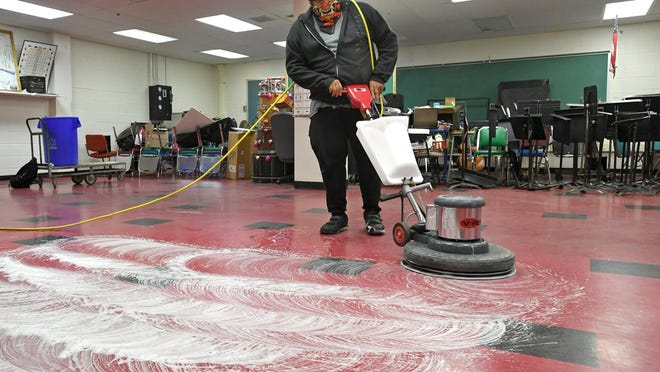 Custodian Aaron Bretz, 21, cleans the tile floors in a classroom July 22 at Strong Vincent Middle School in Erie. This classroom won't be used for instruction during the 2020-21 school year, but the cleaning protocol shows how school officials are working to slow the spread of COVID-19, the new coronavirus, throughout the building.