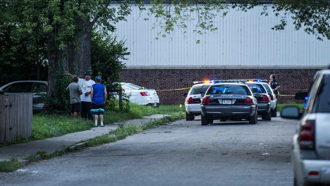 Neighbors in the 2700 block of Newton Avenue watch as police process the scene of a fatal officer involved shooting Monday night.