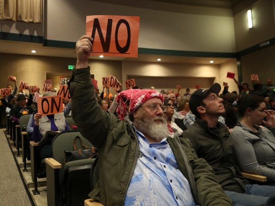 Audience members hold up signs Wednesday during Rep.