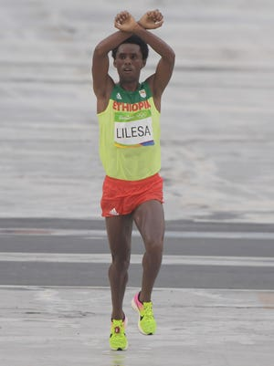 Feyisa Lilesa (ETH) holds up an X gesture as he crosses the finish line in the men's marathon.
