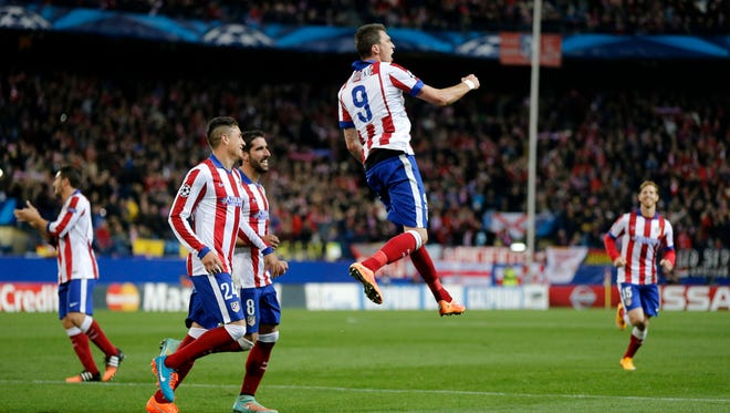 Atletico's Mario Mandzukic celebrates after scoring the fourth goal of his team and his hat-trick during the Champions League Group A soccer match between Atletico de Madrid and Olympiakos.