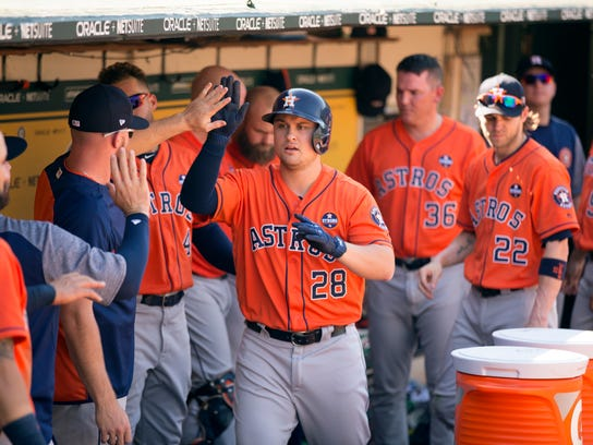 Houston Astros' J.D. Davis (28) gets high fives from this teammates after leading off with a solo home run against the Oakland Athletics in the eighth inning of a baseball game, Sunday, Sept. 10, 2017, in Oakland, Calif. The A's won 10-2, and swept the four-game series. (AP Photo/D. Ross Cameron)