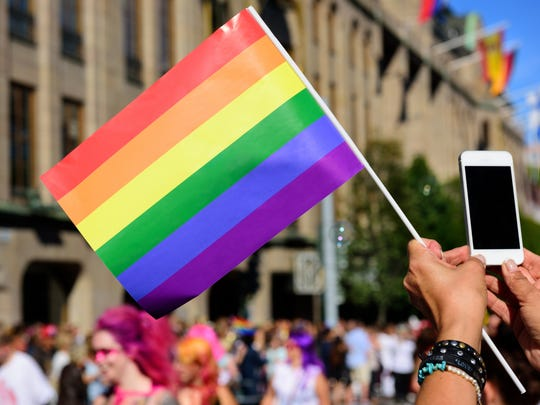 The pride flag and a spectator taking pictures with mobile phone.