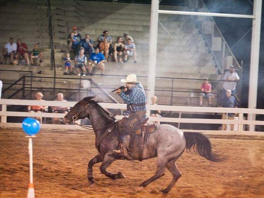 A rider in Alexandria Fair's 2016 cowboy-mounted shooting contest fires blanks to pop balloons from horseback.