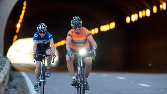 Bob Lewis (right) and Bob Young emerge from the Queen Creek Tunnel, March 14, 2015, at the start of the Mining Country Challenge bicycle tour.