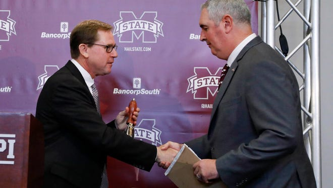 Mississippi State athletic director John Cohen, left, hands new head football coach Joe Moorhead a traditional cowbell.