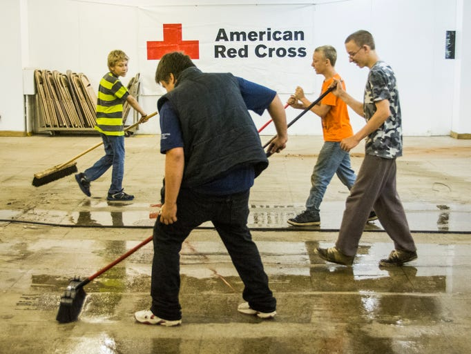Jack West, Isaiah Freeman, Joey Freeman, and Seth Hilson push water and dirt in the basement of the local Red Cross Chapter Monday. Boy Scout Pack 116 worked a day of community service by helping the Red Cross of Richland and Ashland Counties clean out their basement of their North Park building. Taylor Steamer provided a technition, a power washer and cleaning supplies for the job. The pack is sponsored by American Legion Post 16.
