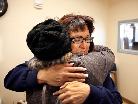 """In this Thursday, Dec. 21, 2017 photo, Joleen Valencia, who was held past her scheduled parole date while serving a drug-trafficking sentence, embraces social worker Sheila Ciminera at The Pavilions, a residential re-entry program in Los Lunas. New Mexico prison records show the state has held hundreds of inmates, like Valencia, past their projected parole dates under a practice widely known as """"in-house parole."""""""