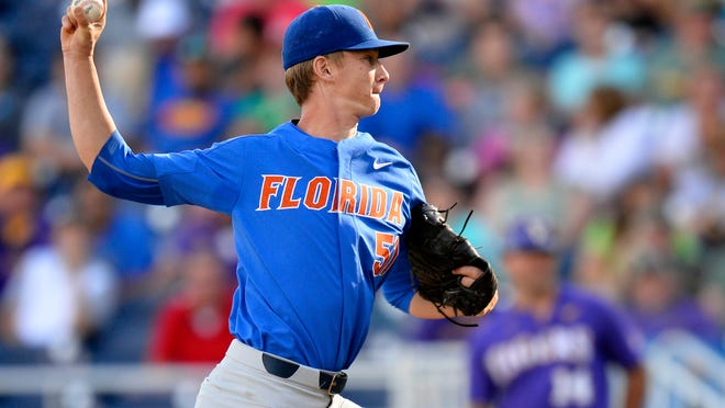 FILE - In this June 26, 2017, file photo, Florida pitcher Brady Singer (51) throws in the first inning of Game 1 of the NCAA College World Series baseball finals against LSU in Omaha, Neb. The top-seeded and defending national champion Gators (42-17) begin regional play Friday having lost six of their last seven, all since clinching the Southeastern Conference's regular-season title. Singer, expected to be a top-five pick in next week's MLB draft, is scheduled to return Saturday after missing two weeks with a strained left hamstring. (AP Photo/Matt Ryerson, File)