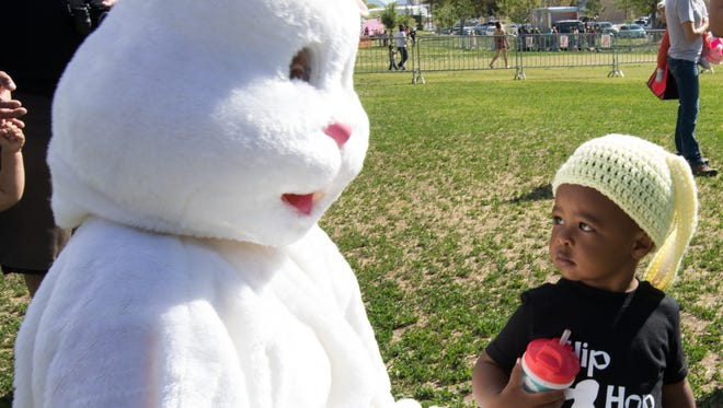 The Easter Bunny greets an unsure youngster at the Springfest event held at Young Park.