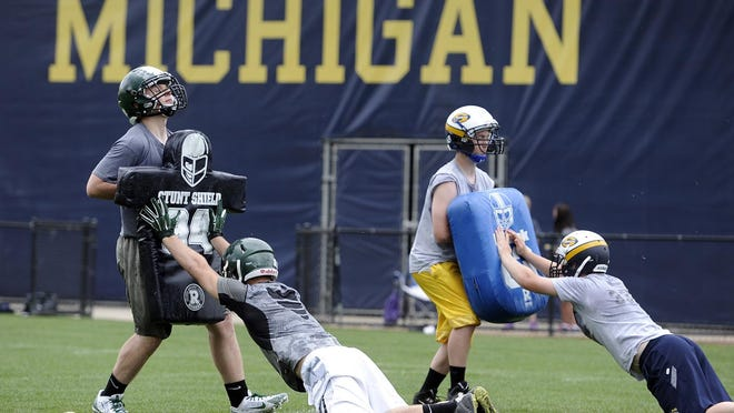 A group of high school lineman get down and dirty while running blocking drills during the University of Michigan's Exposure U football camp, Monday morning, June 15th in Ann Arbor. (Photo by Lon Horwedel/Special to the Detroit News)