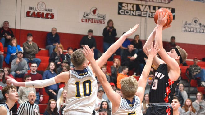 Onaway's Jager Mix (20) shoots over a pair of Wolverine defenders during a Division 4 boys basketball district contest in Onaway last March. With an experienced team back, the Cardinals are hoping to make a run at a district title this winter.