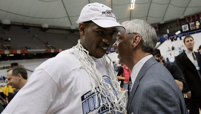North Carolina coach Roy Williams chats with Rashad McCants after defeating Wisconsin 88-82 to win the NCAA East Regional in Syracuse, N.Y. in 2005.