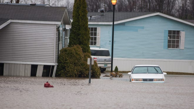 A car sits in flood water Monday, Mar. 28, at the Port of Call mobile home community in Port Huron.