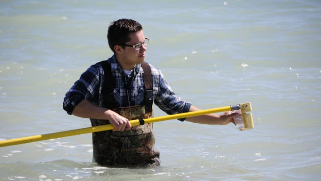 Adam Czubachowski collects a water sample for testing at Holland Road Beach in Port Huron.