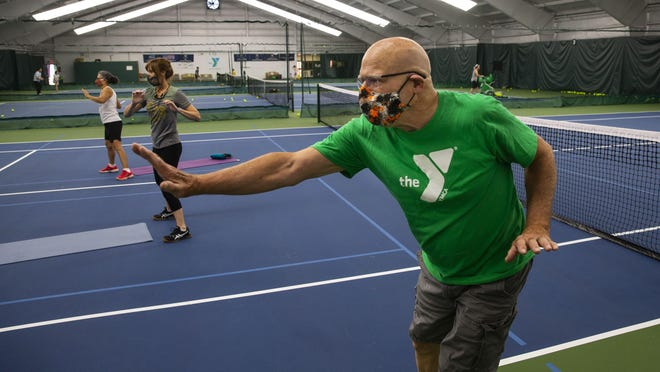 Mark Rauch, 77, right, joins a socially distant, low-impact aerobics class inside the tennis center at the YMCA in Eugene. [Chris Pietsch/The Register-Guard] - registerguard.com