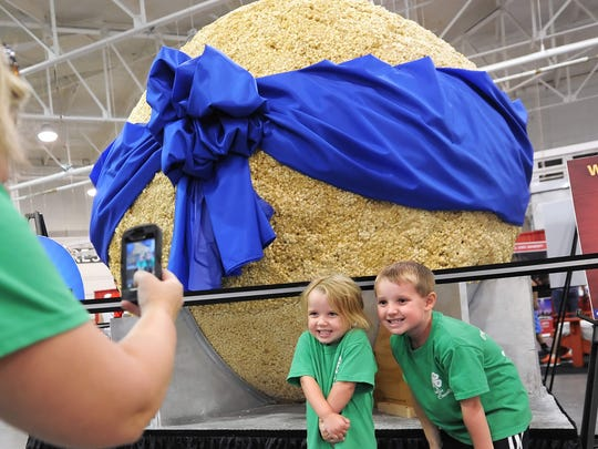 Ella Amrhein, 3 of Brookville, Indiana, and her brother Eli Amrhein, 5, get their photo taken in front of the World's Largest Popcorn Ball by their mom Jodi during the Indiana State Fair on Saturday, August 17, 2013. Matt Detrich / The Star