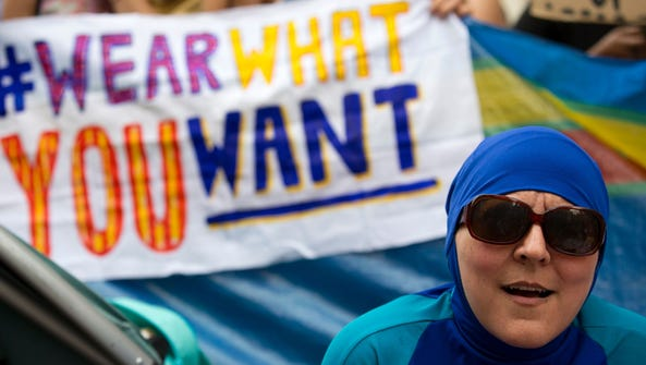 """A woman wearing a """"Burkini"""" joins a protest outside"""