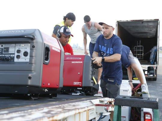 Dallas Mavericks guard J.J. Barea loads up generators for a trip to Puerto Rico after Hurricane Maria.