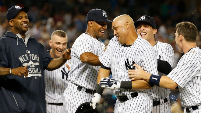 New York Yankees teammates celebrate with New York Yankees Carlos Beltran, third from right, after he hit a ninth-inning, walk-off, sacrifice fly allowing New York Yankees Brett Gardner to score in the Yankees 1-0 victory over the Houston Astros in a baseball game at Yankee Stadium in New York, Monday, Aug. 24, 2015.  (AP Photo/Kathy Willens)