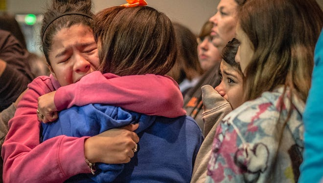 Thirteen year old Kimberly Macias cries as she sees schoolmates at a vigil for the victims of Tuesday's school shoooting in Roswell, N.M. A 12-year-old boy drew a shotgun from a band-instrument case and shot and wounded two classmates at Berrendo Middle School Tuesday morning before a teacher talked him into dropping the weapon and he was arrested, officials and witnesses said.