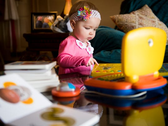 Eva Frank plays with toys at her grandmother's home