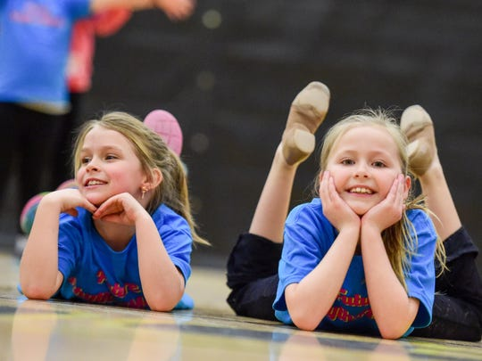 Second-graders Haley Miller (left) and Alicia Young smile as they finish a routine on during the RhythAMettS pom clinic.