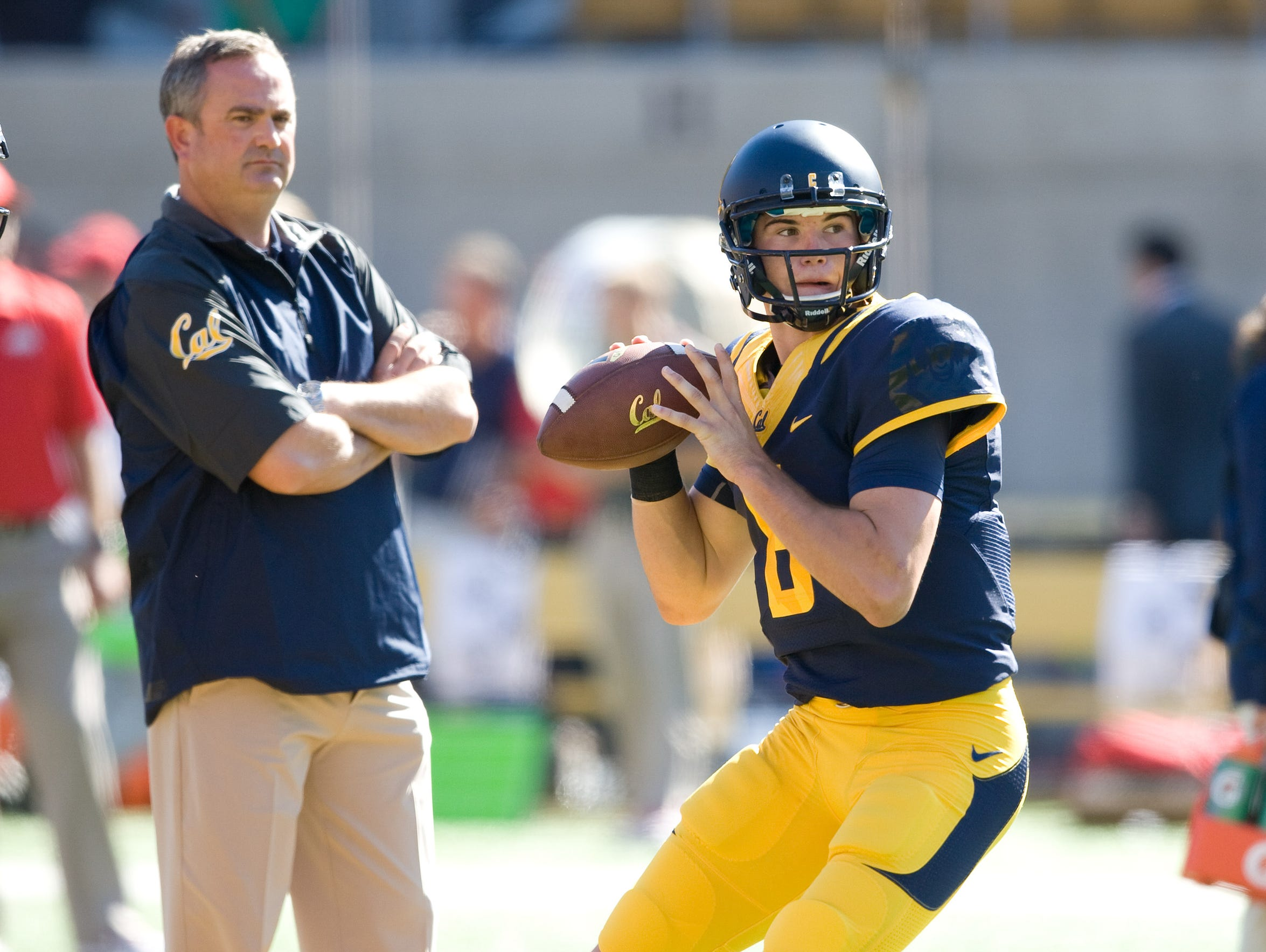 Cal coach Sonny Dykes observes Zach Kline during warmups
