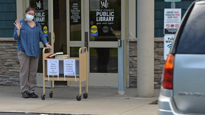 Branch manager Colleen Donaldson, 45, waves to a guest while wheeling out a cart of books at the Lincoln Community Center, 1255 Manchester Road in Fairview Township on June 15, when a curbside pickup policy for library materials was made available. The next phase of reopening starts Monday.