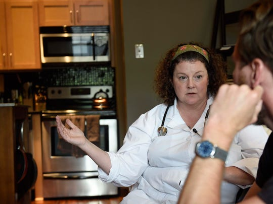 Julia Morris, a family nurse practitioner for Dose, gives treatment options to a patient in his apartment in Nashville.