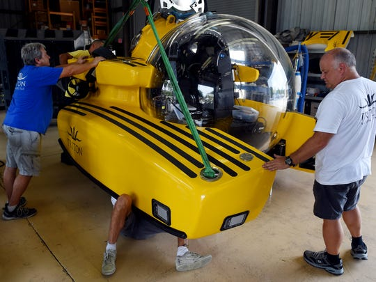 Triton Submarine LLC employees Tim Kutsin (from left), Colin Quigley and Kelvin Magee attach one of two main ballast tanks on a three-person submarine, Wednesday, Aug. 2, 2017, at the shop in Vero Beach. Triton was formed in 2008 and has completed 14 submersibles over the last nine years.