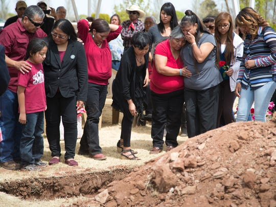 Family and friends surround the grave of Loreal Tsingine.