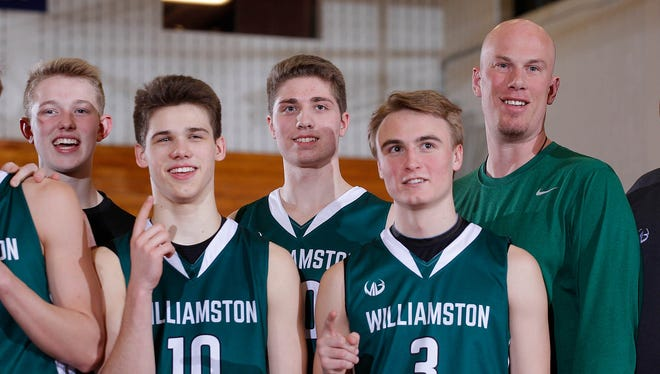 Williamston coach Jason Bauer, right, stands with players after they won their MHSAA regional title with a 51-40 win over Portland, Wednesday, March 15, 2017, in Ionia, Mich.