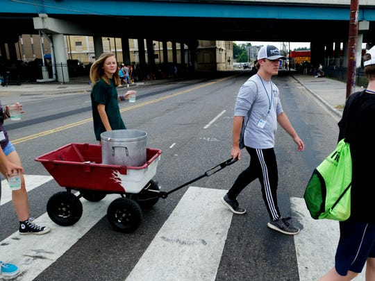 Matthew Cook pulls the water wagon across Broadway during the Win Our World (WOW) Urban Ministry program at St. John's Lutheran Church during a water handout along Broadway in Knoxville, Tennessee on Thursday, July 20, 2017. Because temperatures have been so hot, the youth provided water from a large pot to homeless in the mission district a couple of times this week.