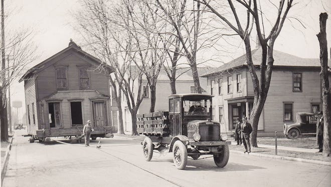 """Oshkosh Corp.'s first vehicle, """"Old Betsy,"""" pulls a house. The truck is still displayed at the company's offices in Oshkosh."""
