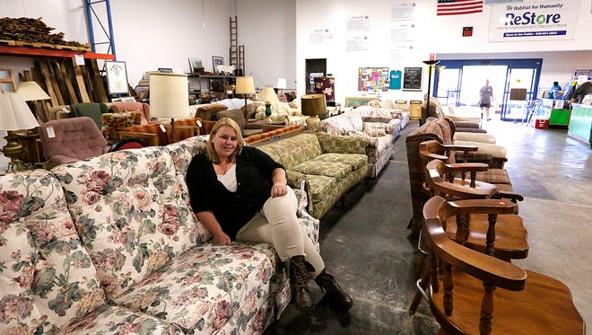 Habitat for Humanity President of Board of Directors, Julie Woznik sits on one of the many pieces of furniture in the ReStore store on Scott Street.
