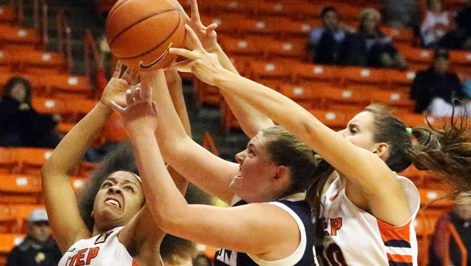 UTEP's Najala Howell, left, and Wiktoria Zapart, right, reach for a rebound against Alyssa Rader, center, of Northern Arizona on Tuesday night in the Don Haskins Center.