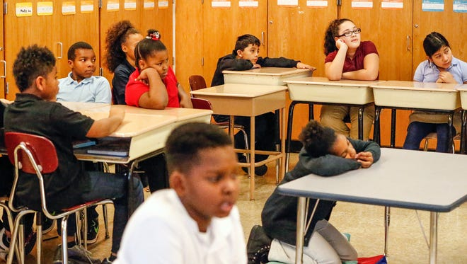Students in the classroom of fourth-grade teacher Heather Powell listen as volunteer Kevin Givens reads the book 'Tsunami' out loud at Wendell Phillips School 63 on Tuesday, Nov. 29, 2016. IPS launched a program with its most at-risk schools called Real Men Read, where volunteer male mentors come into fourth-grade classrooms once a month to read aloud. The volunteers intend to be role models for the students and hope it will help move the needle on literacy. This is the second visit for Givens who is a Indianapolis Fire Department recruiter and former fire fighter of 32-years.