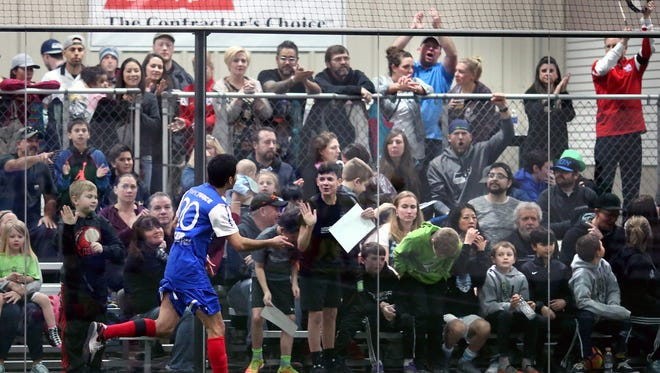Olympic Force player Luis Enrique Hidalgo plays to the crowd after scoring a goal against the Oly Town Artesians on Saturday night at the Olympic Sports Center in Bremerton.