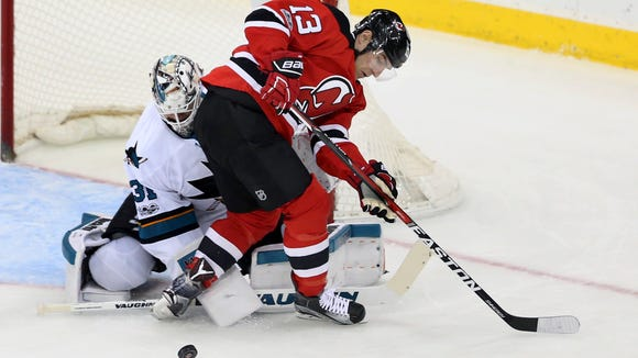 San Jose Sharks goalie Martin Jones (31) defends his net as New Jersey Devils left wing Michael Cammalleri (13) plays the puck during the first period of an NHL hockey game, Sunday, Feb. 12, 2017, in Newark, N.J. (AP Photo/Mel Evans)