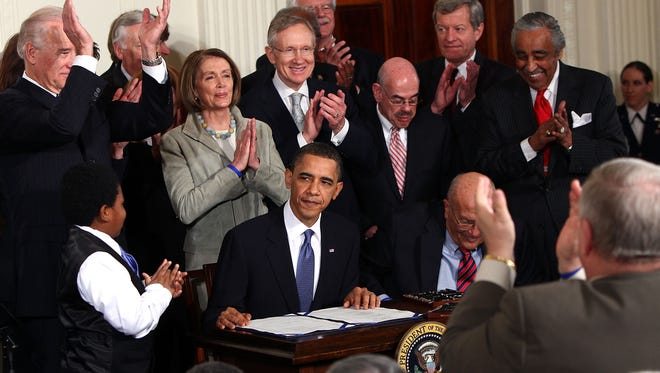 President Obama is applauded after signing the Patient Protection and Affordable Care Act March 23, 2010. Since then, at least 14 bills have made changes to the law.