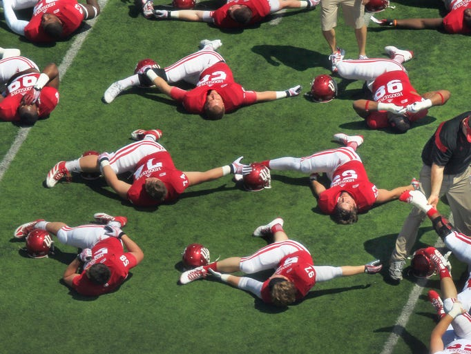 Indiana University football players limber up before the start of the Indiana Hoosiers' Spring Football Game at Memorial Stadium in Bloomington on Saturday, April 12, 2014.